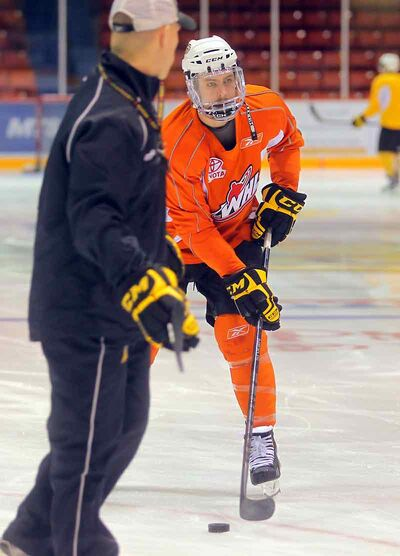 Assistant coach Darren Ritchie watches Wheat King captain Ryan Pulock skate with a full faceshield in a recent practice.