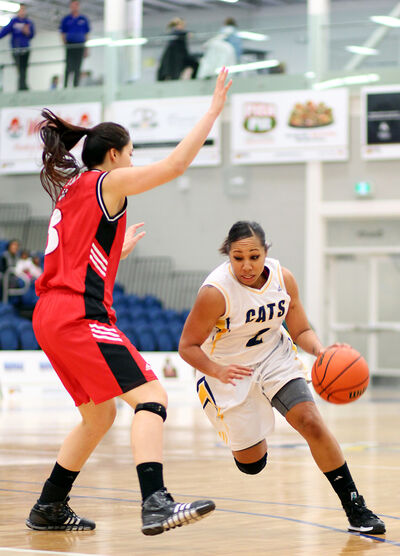 Aleah Bridges of the Brandon Bobcats dribbles around Kelsey Ngo of the Winnipeg Wesmen during their Canada West women's university basketball game Thursday at the Healthy Living Centre.