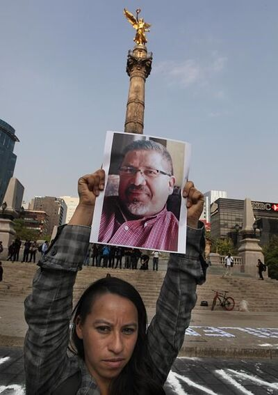 """A photojournalist holds up a photocopy of slain colleague Javier Valdez during a protest to call attention to the latest wave of killings of journalists, at the Angel of Independence in Mexico City, Tuesday, May 16, 2017. Valdez, an award-winning reporter who specialized in covering drug trafficking and organized crime, was slain Monday in the northern state of Sinaloa. """"In Mexico they are killing us,"""" wrote a dozen reporters at the monument's base, next to, """"No to silence"""". (AP Photo/Marco Ugarte)"""