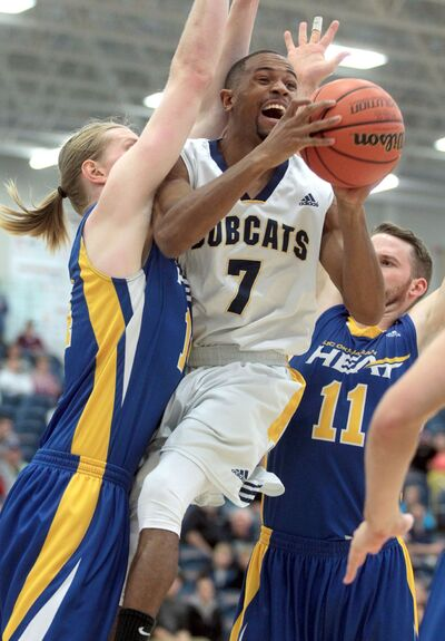 Brandon Bobcats guard Tyvon Cooper looks for an open pass as UBC Okanagan Heat players Ryan Morck, left, and Mitchell Goodwin sandwich him in during a Canada West conference men's basketball game at the Healthy Living Centre on Saturday evening.
