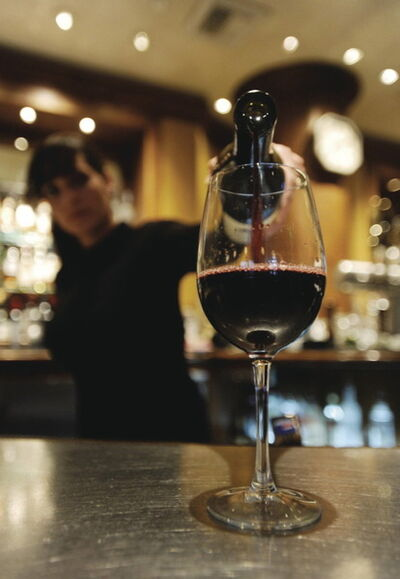 A bartender pours a glass of wine.