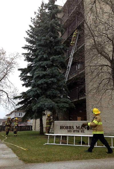 Firefighters extinguish a fire in an apartment at the Hobbs Manor on Saturday morning. Most of the evacuated tenants were back in their apartments that afternoon.