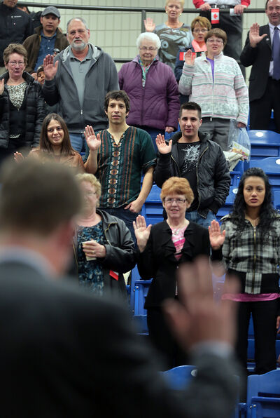 Justice Minister Andrew Swan reads the oath of citizenship as fairgoers reaffirm their citizenship on Wednesday.
