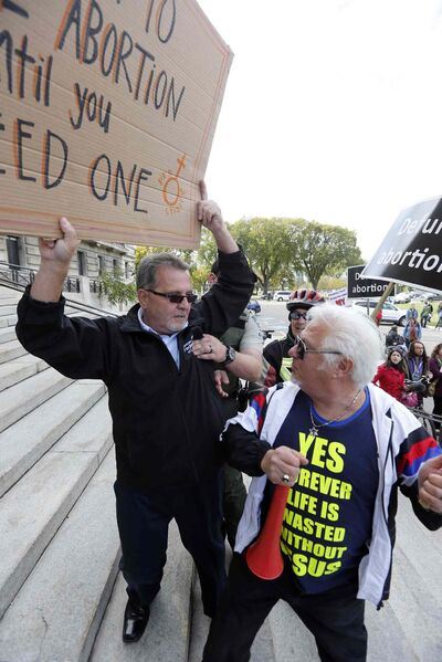 Pro-choice and pro-life protesters demonstrate and square off outside the legislature Thursday.