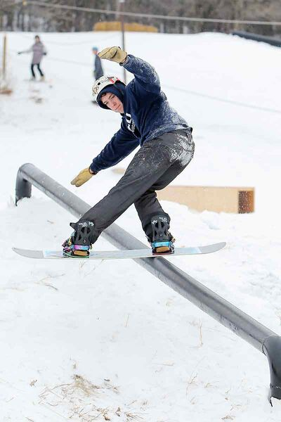 Dylan Martin frontside boardslides a rail during the Brandon Snowboard Club's open house at the snowboard park on Grand Valley Road at the Trans-Canada Highway west of Brandon on Saturday. The open house included a barbecue and a demo from sponsored snowboarders.