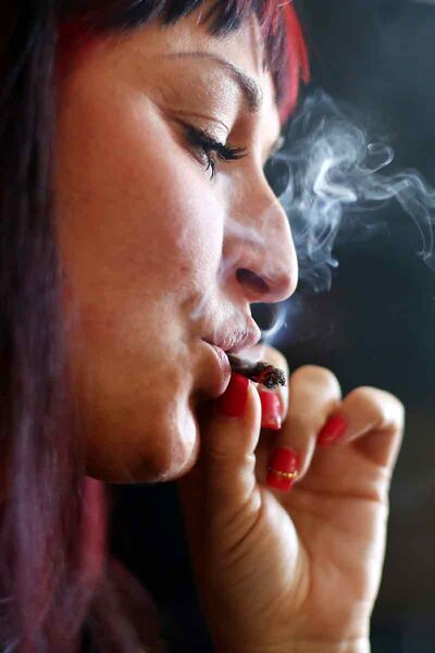 Jade Ridge, CEO and founder of the Canadian Medical Marijuana Clinic based in Brandon, smokes marijuana in the living room of her home.