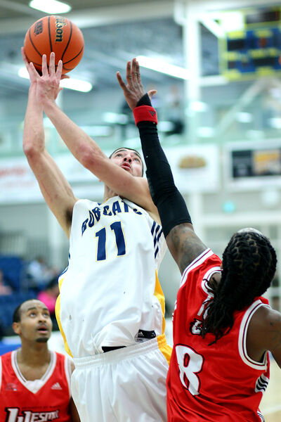 Ali-Mounir Benabdelhak of the Bobcats leaps for a shot as Winnipeg's Steven Wesley goes for the block during the men's game.