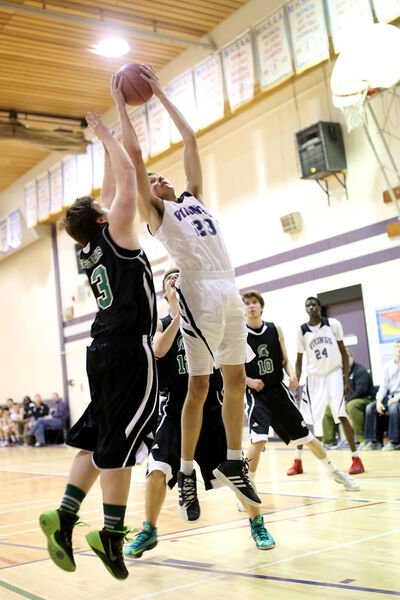 James Klassen of the Vincent Massey Vikings leaps above a member of the Neelin Spartans to grab a rebound in the Westman High School Basketball League varsity boys' final on Thursday at Massey. The Spartans won 87-55 to sweep the city final series.