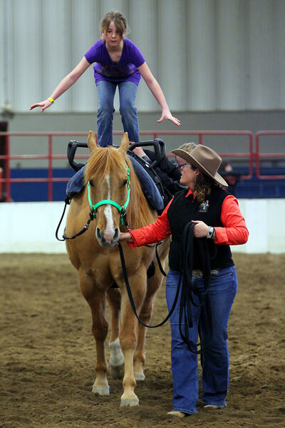 Elena Neufeld, 9, learns how to stand on the back of a horse as instructor Tara Reimer holds the reins during a vaulting class during last April's Horse3 event at the Westoba Agricultural Centre of Excellence. This year's event runs from Good Friday through Easter Sunday.