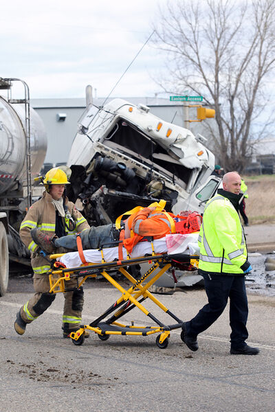 Brandon Fire and Emergency Services members transport the driver of a tanker truck to a waiting ambulance after the collision on Monday.
