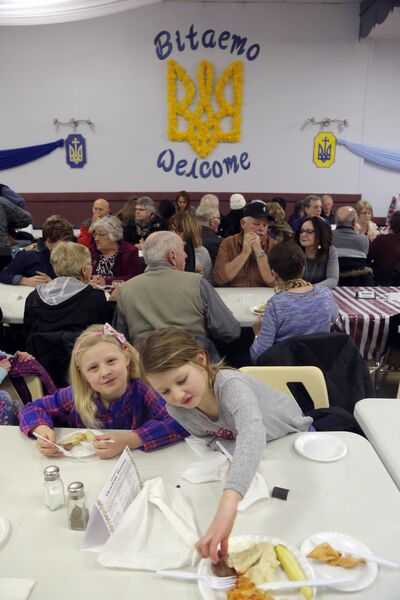 Olivia Wilson, left, and Taylor Patton chow down on perogies at the Ukrainian pavilion on Thursday evening.