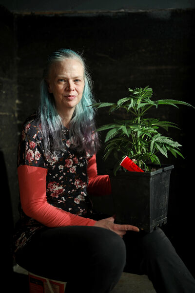 Laurel Roberts with one of her cannabis plants in her home in Hamiota. (Tim Smith/The Brandon Sun)