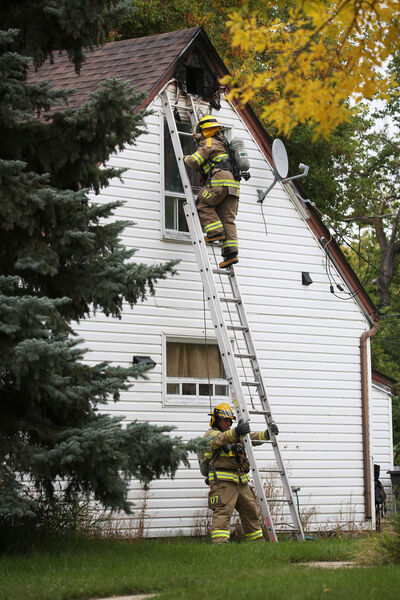 A firefighter with a camera climbs a latter to the attic window of a home in the 1100 block of Eighth Street on Monday afternoon, after a fire that appeared to have started on the top floor was doused. (Matt Goerzen/The Brandon Sun)
