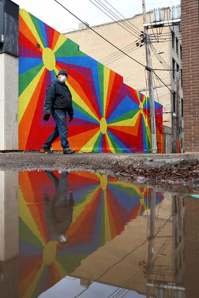 A pedestrian wearing a protective mask is reflected in a puddle while walking past a mural on Rosser Avenue on a warm Tuesday. (Tim Smith/The Brandon Sun)
