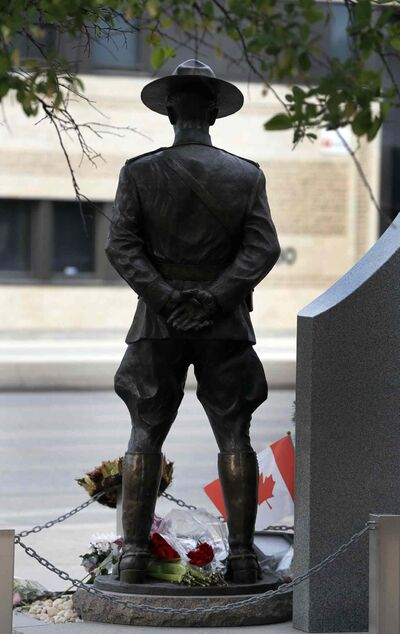 At Winnipeg D Division headquarters the RCMP memorial for Mounties who lost their lives on duty is adorned with flags, wreaths, flowers and messages of condolence on the day of the funerals for RCMP officers killed in Moncton.