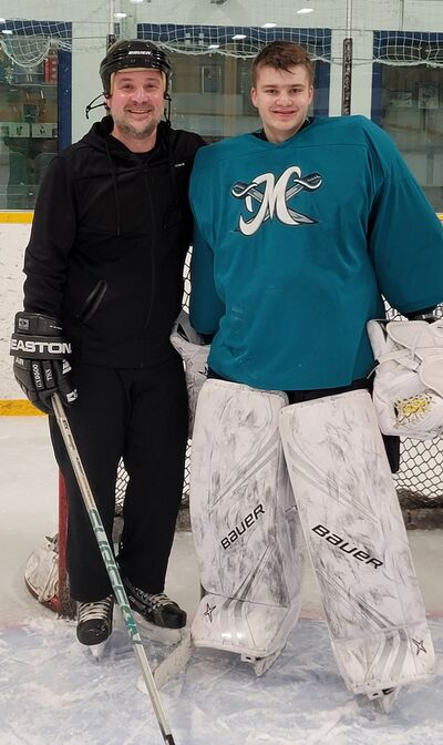 Alex Argyriou poses for a picture with his son Liam McKay-Argyriou at a team practice.
