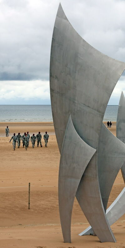 American soldiers walk on Omaha Beach after collecting sand to take back to the U.S. on the 70th anniversary of the D-Day invasion.
