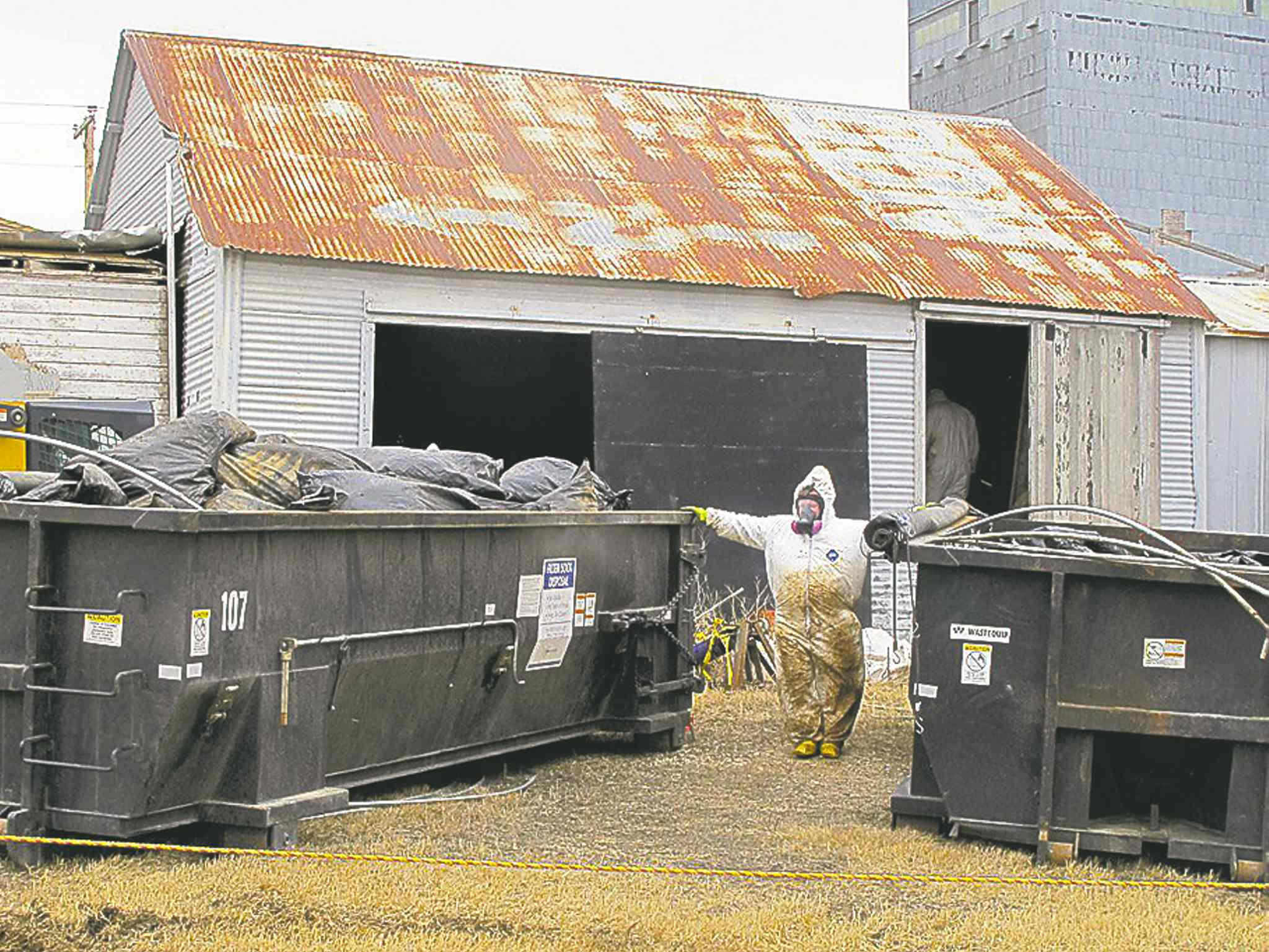 Workers clean up an illegal filter sock dump in Noonan, N.D., on Wednesday.