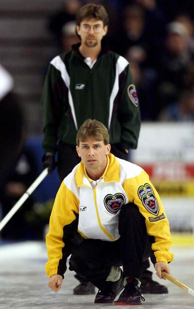 PEI skip Robert Campbell slips in behind Manitoba skip Jeff Stoughton as he watches his rock with during the 16th draw at The Brier in Edmonton Tin 1999. (Chuck Stoody / The Canadian Press Files)
