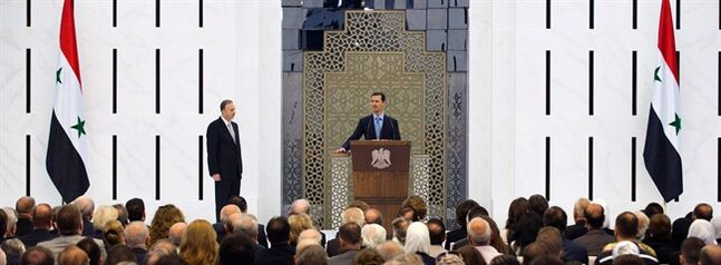 In this photo released by the Syrian official news agency SANA, Syria's President Bashar Assad, center background, is sworn in for his third seven-year term in Damascus, Syria, Wednesday July 16, 2014. Proclaiming the Syrian people winners in a