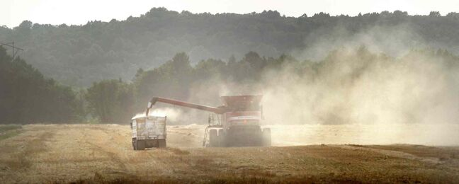 Dust frames a combine against the Manitoba Escarpment near Roseisle, Man. as it dumps grain into a waiting truck. The Manitoba government says it has received personal assurances from the head of CP Rail that the railway will make grain shipments to Thunder Bay a priority.