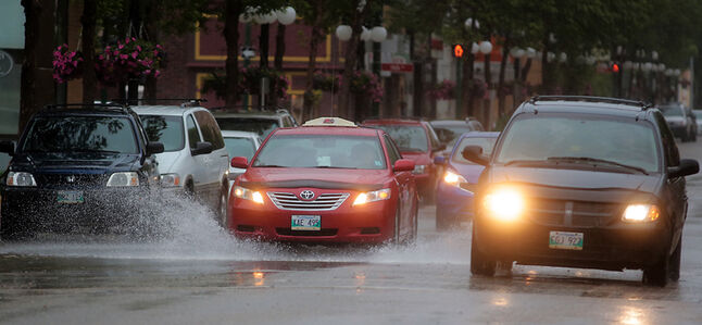 Vehicles travelling on Rosser Avenue splash through the pooled runoff water from the rainfall on Thursday afternoon.