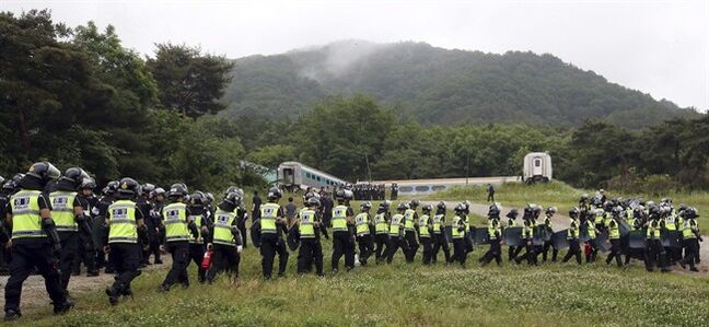 Police officers raid into a religious facility of the Evangelical Baptist Church in Anseong, South Korea, Wednesday, June 11, 2014. Thousands of South Korean police officers stormed a church compound Wednesday in their hunt for a fugitive billionaire businessman over April's ferry sinking that left more than 300 people dead or missing, officials said. (AP Photo/Yonhap, Shin Young-geun) KOREA OUT