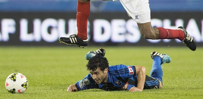 A player from C.D. Fas leaps over Montreal Impact's Felipe Martins during second half CONCACAF Champions League soccer action in Montreal, Tuesday, August 5, 2014. THE CANADIAN PRESS/Graham Hughes