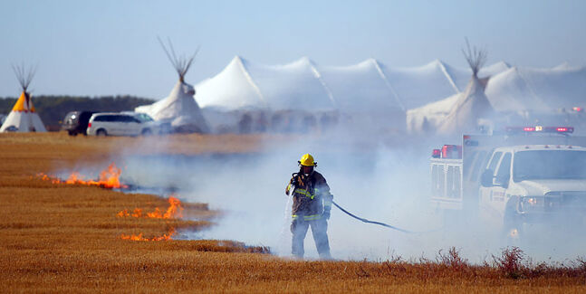 A firefighter battles a fast-moving grass fire that got out of control at the Treaty 1-11 gathering south of the Brandon Municipal Airport on Tuesday afternoon.
