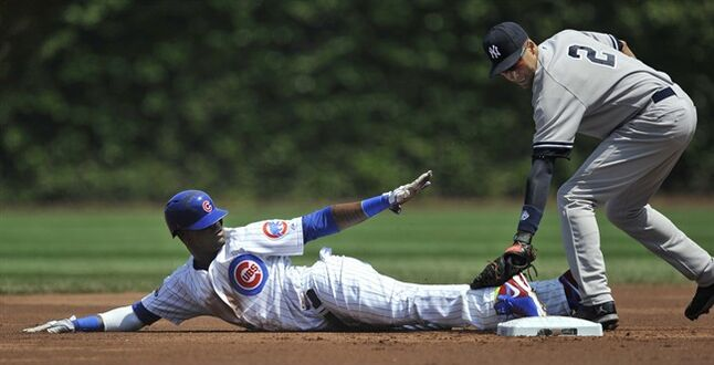 Chicago Cubs' Junior Lake looks to the second base umpire after stealing second while New York Yankees shortstop Derek Jeter tries to apply the tag during the second inning of an interleague baseball game in Chicago, Wednesday, May 21, 2014. (AP Photo/Paul Beaty)