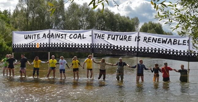Demonstrators protest with a human chain against planned coal mines at the Neisse river , German-Polish border near Gross Gastrose, Germany Saturday Aug. 23, 2014. Several thousand people have formed a human chain across the German-Polish border in a protest against open-cast mining for brown coal, also known as lignite, in the region. (AP Photo/dpa, Patrick Pleul)