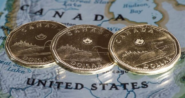 Canadian dollar coins, or Loonies, are displayed on a map of North America January 9, 2014 in Montreal. THE CANADIAN PRESS/Paul Chiasson