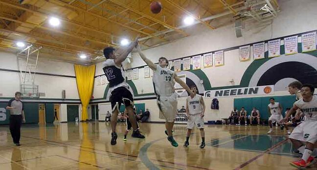 Jeremy Lucio of the Vincent Massey Vikings shoots a three-pointer over the reach of Dylan Minshull of the Neelin Spartans during Saturday night's final of the Neelin Invitational Tournament at Neelin High School. Neelin won 71-39.