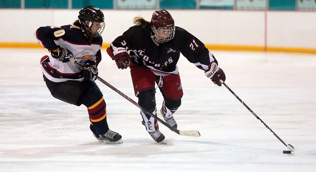 Brittany Phillips, right, moves the puck up the ice for the Assiniboine Community College Cougars as Courtney Uruski gives chase during Sunday's women's Senior B provincial championship final against Winnipeg's Rage II at the Kinsmen Arena.