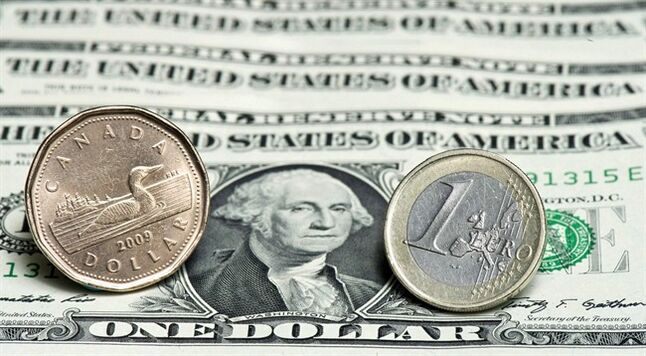 A Canadian dollar, left, and a Euro are seen next to a series of U.S. dollars in this January 26, 2011 photo in Montreal. THE CANADIAN PRESS/Paul Chiasson