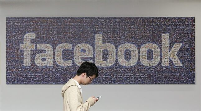 In this June 11, 2014 photo, a man walks past a Facebook sign in an office on the Facebook campus in Menlo Park, Calif. The Proceedings of the National Academy of Sciences says that as a private company, Facebook had no obligation to adhere to rules on the use of human subjects in the study. But the journal says Facebook's data collection practices may have violated scientific principles requiring the consent of study subjects. (AP Photo/Jeff Chiu)