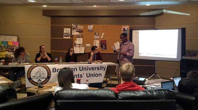 Baraa Salama (right), an international student at Brandon University, speaks on his motion recommending Raymond Thomson resign from his position with the Brandon University Students' Union at BUSU's semi-annual general meeting on Tuesday. Thomson is seated at the far right of the table.