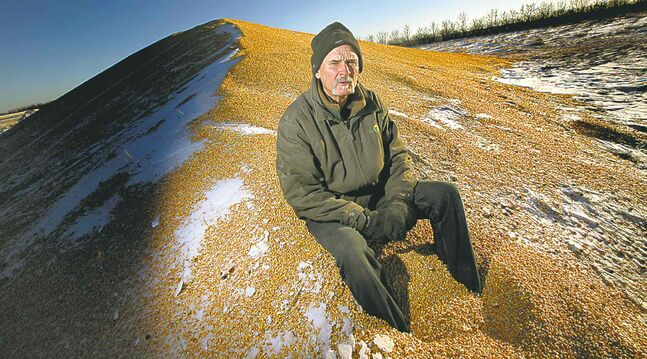 Kent Oatway -- sitting on a pile of corn -- is one farmer who's been affected by the crop congestion problems.
