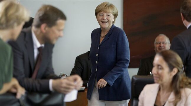 German Chancellor Angela Merkel smiles as she arrives for the weekly cabinet meeting at the chancellery in Berlin, Germany, Wednesday, July 9, 2014. (AP Photo/Michael Sohn)