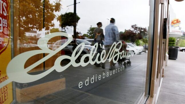 FILE - In this Wednesday, June 17, 2009, file photo, shoppers are reflected in the window as they walk past an Eddie Bauer store, in Seattle. Jos. A. Bank Clothiers Inc. said Friday, Feb. 14. 2014, it is buying the parent company of Eddie Bauer in a cash-and-stock deal valued at $825 million that will help strengthen its men's wear business and diversify its offerings. (AP Photo/Elaine Thompson, File)