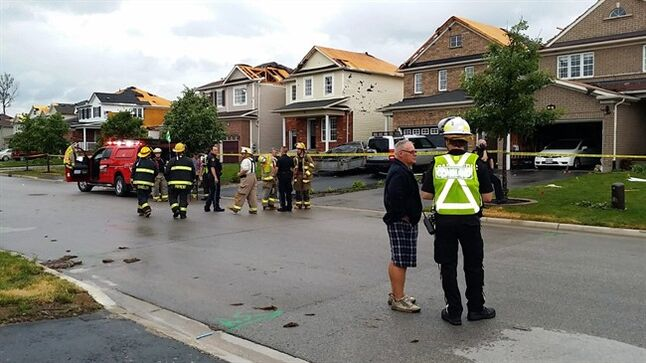 People stand in the street to look at damage to houses in Angus, near Barrie, Ontario on Tuesday June 17, 2014. Provincial police say there are reports of some minor injuries after severe weather ripped through the central Ontario community of Angus. THE CANADIAN PRESS/Christopher Bentley