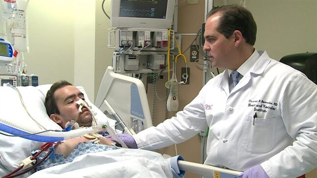 This handout photo provide by the University of Pittsburgh Medical Center, taken March 5, 2014, shows Dr. Christian Bermudez of the University of Pittsburgh Medical Center checking patient Jon Sacker, who was being treated with an experimental device called the Hemolung that acts like dialysis for lungs. Doctors credit the experiment with buying Sacker time to improve enough to undergo a lifesaving double lung transplant later that month. (AP Photo/University of Pittsburgh Medical Center)