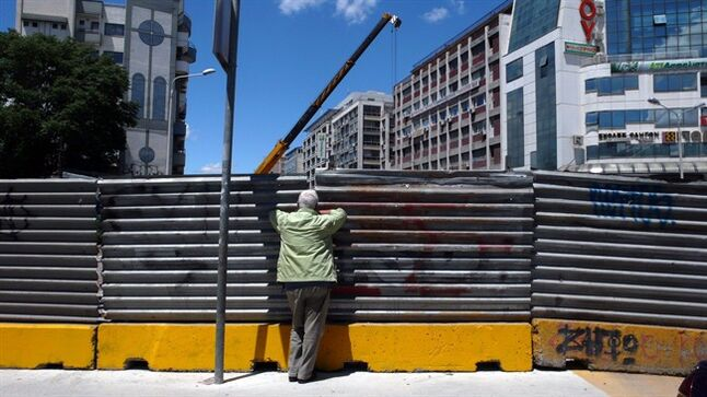 A man looks at a construction site from a small aperture from behind a sheet of metal fencing, in northern Greek city of Thessaloniki on Monday, June 2, 2014. Greece's trade federation said Monday that some 31 percent of all shops in the city center remain unoccupied as a result of the country's acute financial crisis that has seen unemployment hit record-high levels amid a six-year recession. The federation said the number of closed shops was slightly down compared to its last survey about six months ago. (AP Photo/Nikolas Giakoumidis)