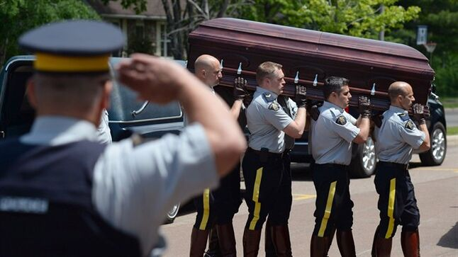 RCMP carry the casket of Cst. Douglas James Larche into Wesleyan Celebration Centre for visitation in Moncton on Monday June 9, 2014. THE CANADIAN PRESS/Sean Kilpatrick