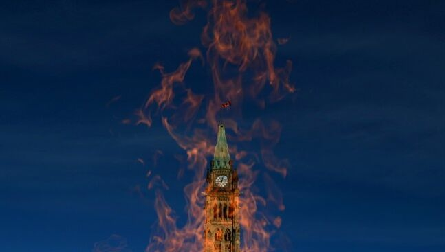 The Peace Tower is pictured through the Centennial Flame on October 23, 2013. THE CANADIAN PRESS/Sean Kilpatrick
