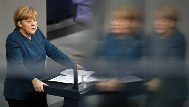 German Chancellor Angela Merkel gestures during a government statement about Europe at the German federal parliament, Bundestag, in Berlin, Germany, Wednesday, Dec. 18, 2013. The reflections caused by windows at the visitors tribune. (AP Photo/Michael Sohn)