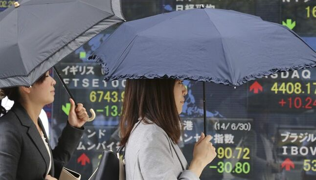 People walk by an electronic stock board of a securities firm in Tokyo Tuesday, July 1, 2014. Shares were mostly lower in Asia on Tuesday as investors shrugged off signs that Chinese manufacturing is regaining momentum. (AP Photo/Koji Sasahara)