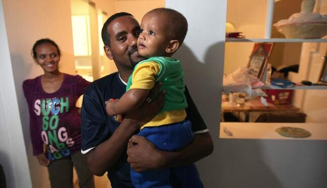 Aman Ghebrezgiabher, from Eritrea, holds son Naod as his wife Selam, due in October, looks on in their inner-city apartment. Ghebrezgiabher has multiple medical needs the province will now finance.