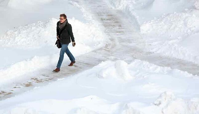 A student makes his way across the sidewalks on campus at Brandon University on Monday morning.