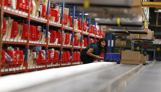 Leidy Gomez checks the movement on a conveyor belt while packaging toys at the Barnes & Noble distribution center,, Dec. 11, 2012, in Monroe Township, N.J. THE CANADIAN PRESS/AP, Julio Cortez
